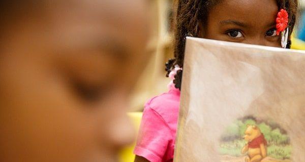 Young girl peeking over her book.