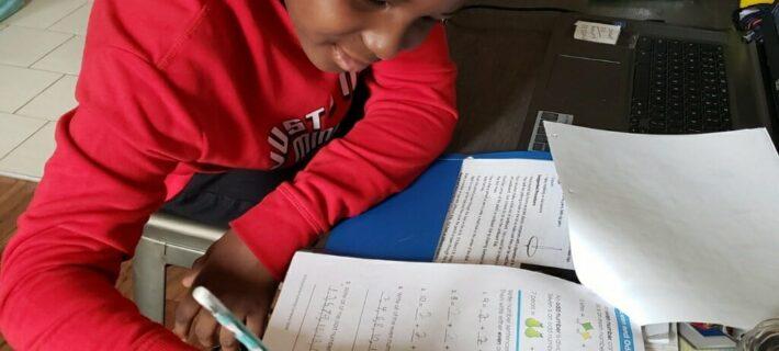 Nakoa does math work at his table.